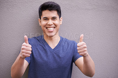 Buy stock photo Portrait of a young man showing thumbs up while standing outside
