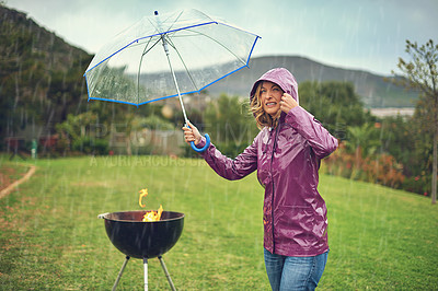 Buy stock photo Shot of a woman holiding an umbrella while trying to barbeque in the rain