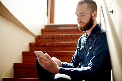 Buy stock photo Cropped shot of a young man using his digital tablet while sitting on a staircase at home