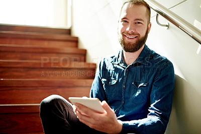 Buy stock photo Cropped portrait of a young man using his digital tablet while sitting on a staircase at home