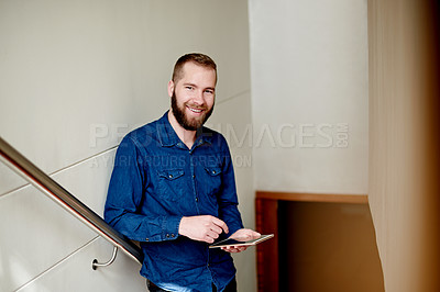 Buy stock photo Cropped portrait of a young man using his digital tablet while standing on a staircase at home