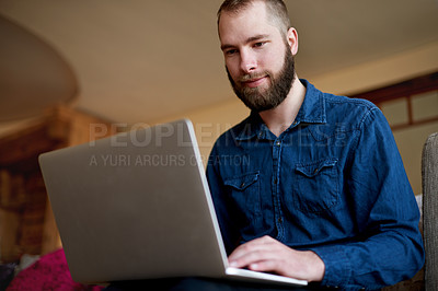 Buy stock photo Cropped shot of a young man using his laptop while sitting on a sofa at home
