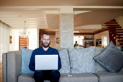 Buy stock photo Shot of a man using his laptop while sitting on the sofa at home