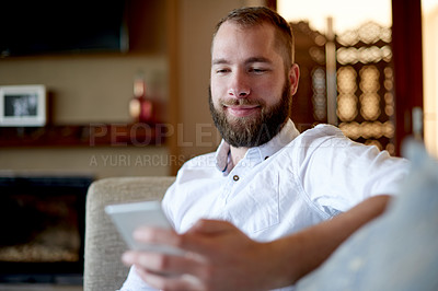 Buy stock photo Shot of a young man using a phone on the sofa at home