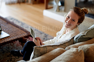 Buy stock photo Cropped portrait of a young woman using her tablet while sitting on the sofa at home