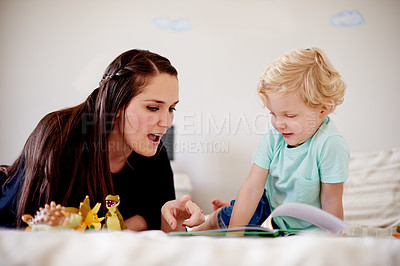 Buy stock photo Shot of a mother reading to her little boy at home