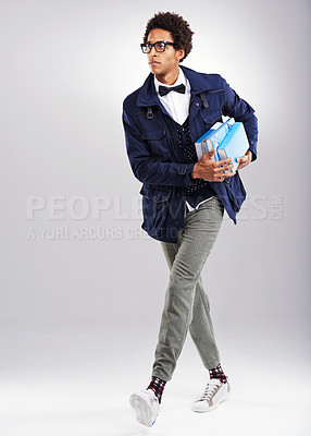 Buy stock photo Studio shot of a stylishly dressed student holding his books against a gray background