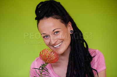Buy stock photo Shot of an attractive young woman with dreadlocks holding a flower against a green background