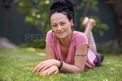 Buy stock photo Portrait of a woman with dreadlocks lying on the grass