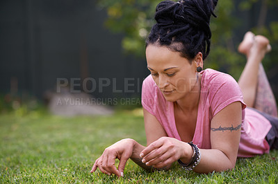 Buy stock photo Shot of a woman with dreadlocks lying on the grass