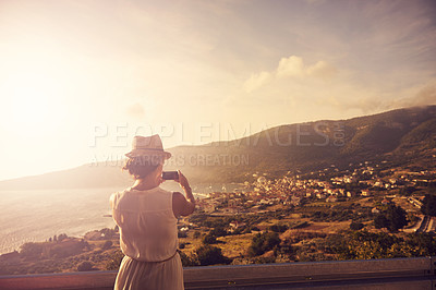 Buy stock photo Shot of a young woman taking a picture of a scenic view with her cellphone