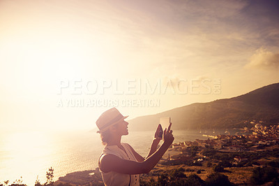 Buy stock photo Shot of a young woman taking pictures of beautiful views with her tablet