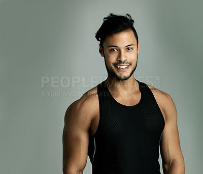 Buy stock photo Studio portrait of an athletic young man posing against a gray background