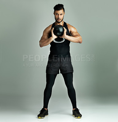 Buy stock photo Studio shot of a young man working out with a kettle bell against a gray background