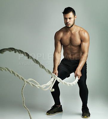 Buy stock photo Studio shot of a young man working out with a heavy rope against a gray background