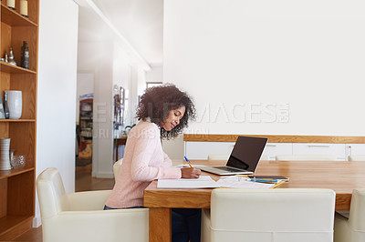 Buy stock photo Cropped shot of a young woman working on her laptop at home