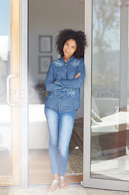 Buy stock photo Portrait of a happy young woman standing in the doorway of her home