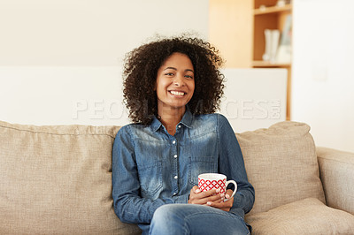 Buy stock photo Portrait of a young woman relaxing on the sofa with a beverage at home