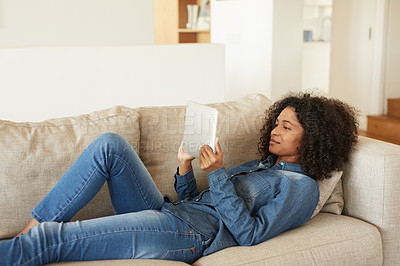 Buy stock photo Shot of a young woman relaxing on the sofa with her digital tablet at home