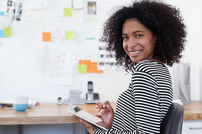 Buy stock photo Portrait of a young designer working on her digital tablet in an office