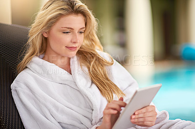 Buy stock photo Shot of a young woman relaxing with her digital tablet at a day spa