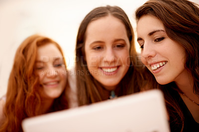 Buy stock photo Shot of girlfriends using a digital tablet together outdoors
