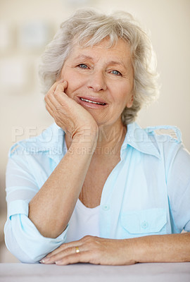 Buy stock photo Portrait of a happy senior woman sitting with her hand on her chin