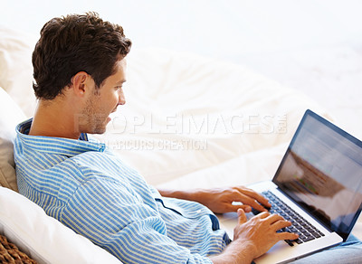 Buy stock photo Man sitting on sofa and browsing internet on laptop