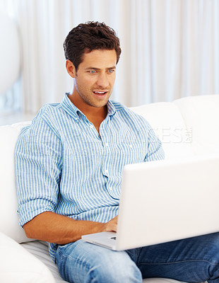 Buy stock photo Surprised man sitting on sofa and browsing internet on laptop