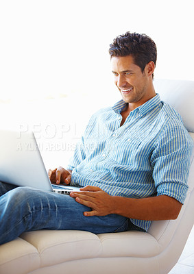 Buy stock photo Happy man sitting on a sofa using laptop and smiling