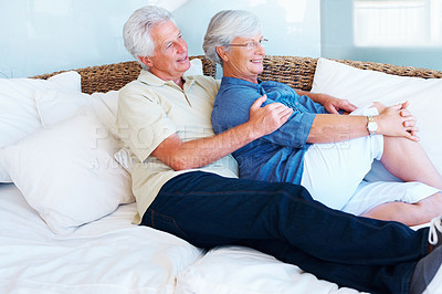Buy stock photo Senior couple sitting on a sofa and looking away