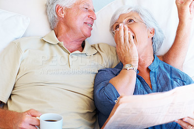 Buy stock photo Happy senior couple relaxing on sofa and reading newspaper
