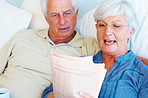Senior couple relaxing on sofa and reading newspaper