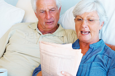 Buy stock photo Senior couple relaxing on sofa and reading newspaper