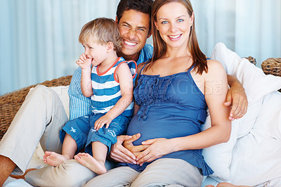 Buy stock photo Portrait of cute family sitting on a sofa and smiling