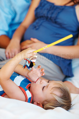 Buy stock photo Closeup of young kid lying on sofa with thumb in mouth and playing with a paper windmill
