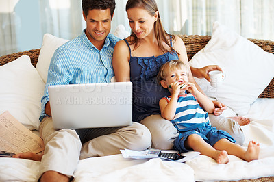 Buy stock photo Family relaxing together on a couch using their home laptop