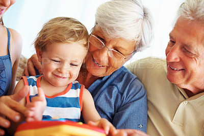 Buy stock photo Young kid playing a toy with his family