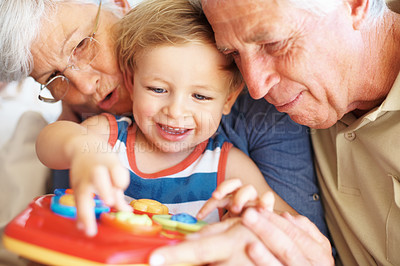 Buy stock photo Closeup of boy playing a toy with his grandparents