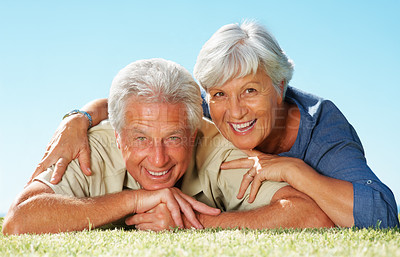 Buy stock photo Closeup of senior couple lying on the grass and smiling
