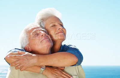 Buy stock photo Closeup of senior couple enjoying the peaceful weather with woman embracing man from behind