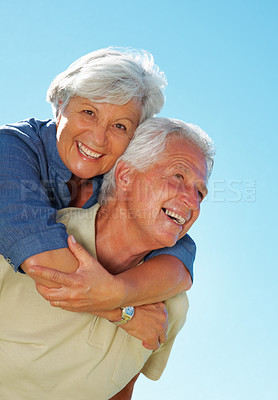 Buy stock photo Portrait of senior man giving woman a piggyback ride against sky