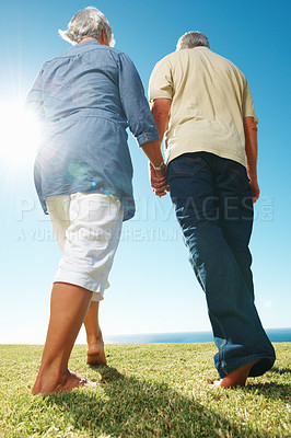 Buy stock photo Rear view of senior couple holding hands and walking on grass