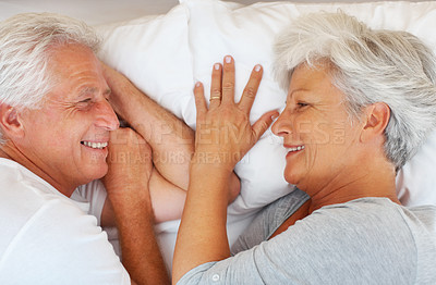 Buy stock photo Closeup of senior couple lying on bed and smiling