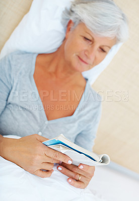 Buy stock photo Senior woman sitting on bed and reading a novel