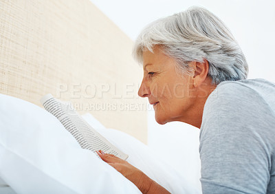 Buy stock photo Closeup of senior woman lying in bed reading a book