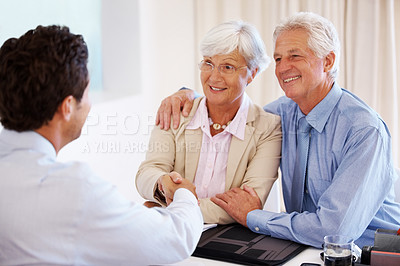Buy stock photo Portrait of a happy mature couple shaking hands with their financial advisor in an office