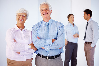 Buy stock photo Senior couple standing in front with two business colleagues talking in background