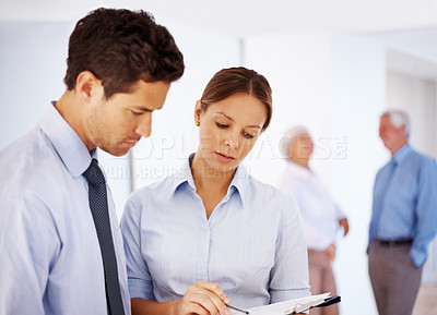 Buy stock photo Busy business professionals looking at reports with people standing in blur background