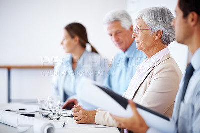 Buy stock photo Portrait of an old businesswoman paying attention at seminar sitting amongst colleagues